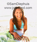 Portrait of a very pretty young woman laying on the beach, facing the camera and smiling beautifully.